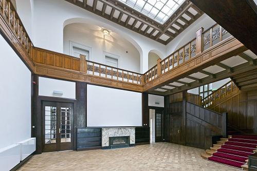 Blick in den funktionalistischen Innenraum mit Holztreppe, Balustrade und modernem Gaskamin